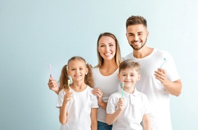 young family in white shirts holding up toothbrushes