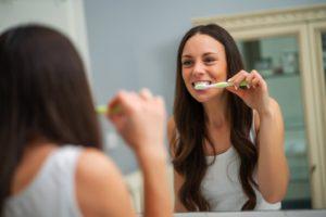 woman in white shirt brushing teeth at home