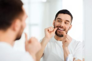 Man carefully flossing teeth to prevent oral health problems